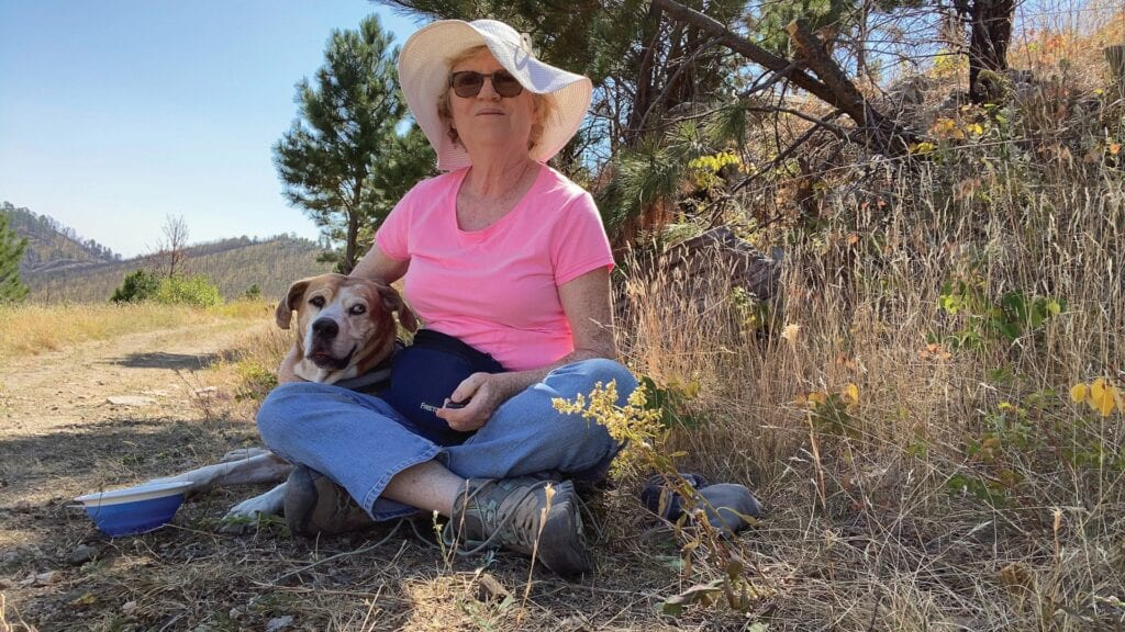 Jeanne Martin and her hound mix, Chyna, stopped in Custer State Park, S.D., during a crosscountry journey where Ms. Martin is collecting photos and videos for a creative/travel blog project she plans to publish upon returning to her home in West Palm Beach this winter. PHOTO BY JEANNE MARTIN